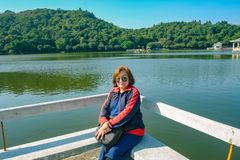 Senior women tourist Sitting on stone chair beside the Lake on top of the xiqiao mountain foshan. Senior woman tourist Sitting on stone chair beside the Lake on stock image