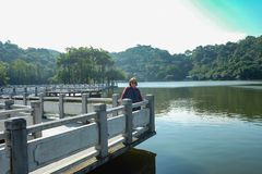 Senior women tourist stand beside the Lake on top of the xiqiao mountain foshan city china stock photography