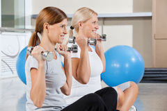 Senior women using dumbbells in gym Stock Photos