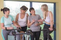 Senior women using spinning bikes Royalty Free Stock Photo