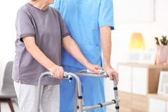 Senior woman walking with assistance of young caregiver. Senior women walking with assistance of young caregiver indoors royalty free stock image