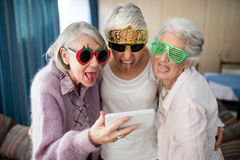 Senior women wearing novelty glasses making face while taking selfie Stock Images