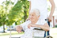 Senior Women in Wheelchair with Caretaker Stock Images