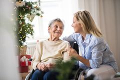 A senior woman in wheelchair with a health visitor at home at Christmas time. A senior women in wheelchair with a health visitor at home at Christmas time royalty free stock photos