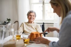 A senior woman in wheelchair with a health visitor sitting at the table at home. A senior women in wheelchair with a health visitor sitting at the table at home royalty free stock photos