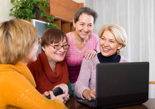 Senior women working with notebook. Happy senior female friends working with notebook using wifi Stock Photography