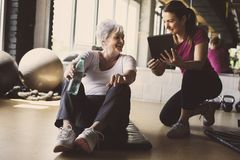 Senior woman workout in rehabilitation center. Senior women workout in rehabilitation center. Personal trainer showing something  on digital tablet Royalty Free Stock Image