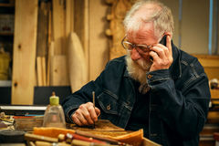 Senior wood carving professional with mobile phone Royalty Free Stock Photos