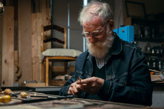 Senior wood carving professional during work Stock Photography