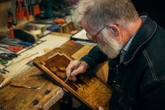 Senior wood carving professional during work.  Stock Image