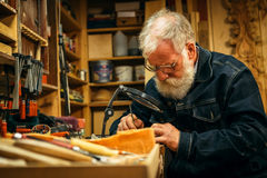 Senior wood carving professional during work Royalty Free Stock Photography