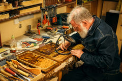 Senior wood carving professional during work.  Stock Photography