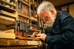 Senior wood carving professional during work Stock Photos