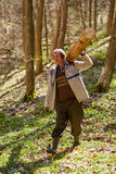 Senior woodcutter with heavy log on shoulder Royalty Free Stock Photography
