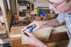 Senior woodworking with edging plane. Senior man doing carpentry with edging plane on workbench stock images
