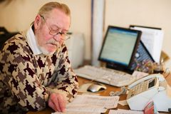 Senior at work place. In office with computer notes and fax Royalty Free Stock Photo