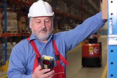 Senior worker with bar code reader Stock Photo