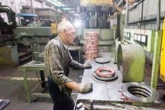 Senior worker checks balancing of detail Royalty Free Stock Photo