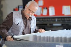 Senior worker cutting metal in factory Stock Photography