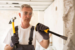 Senior worker demolish wall. With tool on construction site Stock Photography