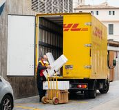 Senior worker discharge DHL parcels from truck in central square. INCA, PALMA DE MALLORCA, SPAIN - MAY 8, 2018: Senior DHL male postmen delivering post parcels stock photos