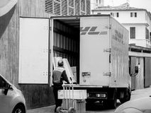 Senior worker discharge DHL parcels from truck in central square. INCA, PALMA DE MALLORCA, SPAIN - MAY 8, 2018: Senior DHL postmen delivering post parcels on the royalty free stock image