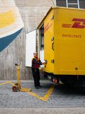 Senior worker discharge DHL parcels from truck in central square. INCA, PALMA DE MALLORCA, SPAIN - MAY 8, 2018: Side view of Senior DHL postmen delivering post royalty free stock photos