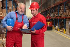 Senior worker and engineer. Two workers in uniforms in warehouse. one is older, one is younger, different activities stock photography