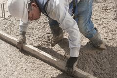 A worker flattening fresh cement Stock Images