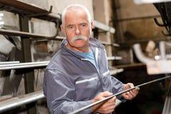 Senior worker holding length metal. Senior worker holding length of metal stock photography