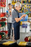 Senior Worker Holding Tool Basket In Store Royalty Free Stock Photos