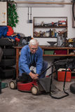 Senior worker with lawn mower in workshop Royalty Free Stock Photos