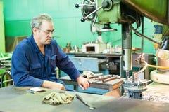 Senior worker operates metalworking machine Stock Photo