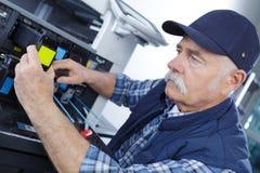 Senior worker repair assistance. Fixing stock photos