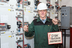 Senior worker standing near electrical panel. Electrician standing near electrical shield with an electric screwdriver and notice board. Inscription in Russian royalty free stock images