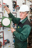 Senior worker standing near electrical panel. Electrician standing near electrical shield with an electric screwdriver and notice board. White helmet stock photography