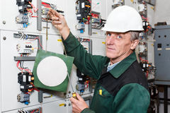 Senior worker standing near electrical panel. Electrician standing near electrical shield with an electric screwdriver and notice board. White helmet royalty free stock photos