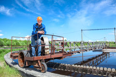 Senior worker standing on waste water treatment unit. On industrial plant Stock Images