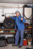 Senior worker with a tire in garage Stock Photography