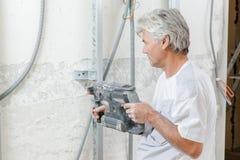 Senior worker using pneumatic drill. Senior worker using a pneumatic drill stock photography