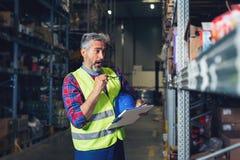Senior worker in warehouse recording stock royalty free stock photos