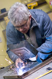 Senior worker welding. A senior worker, grey haired man, welding two pieces of metal Stock Photography