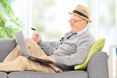 Senior working on laptop and holing credit card Royalty Free Stock Image