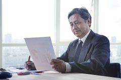Senior working man reading business paper report on working tabl Royalty Free Stock Photos
