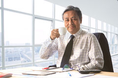Senior working man relaxing with drinking beverage in office roo Royalty Free Stock Photo