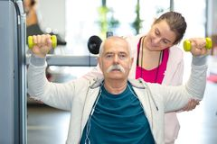 Senior working out with dumbbells and personal trainer. Senior working out with dumbbells and his personal trainer Stock Photos