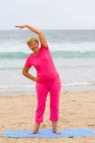Senior workout. Happy senior woman doing fitness workout on beach Royalty Free Stock Images