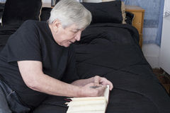 Senior writing from his bed Stock Images