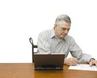 Senior writing with laptop Stock Photos