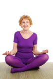 Senior Yoga - Contentment. A fit seventy year old woman in a modified lotus pose smiling in contentment. White background royalty free stock photos
